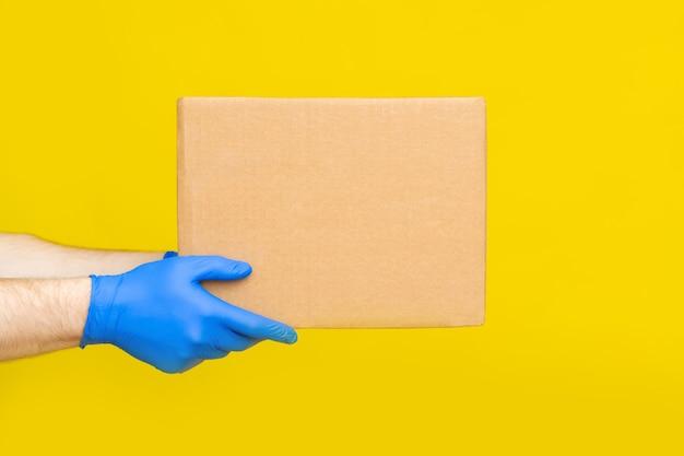 Закройте вверх руки работника доставляющего покупки на дом медицинские перчатки держат пустую картонную коробку на желтой предпосылке. служба коронавируса. онлайн шоппинг. макет.