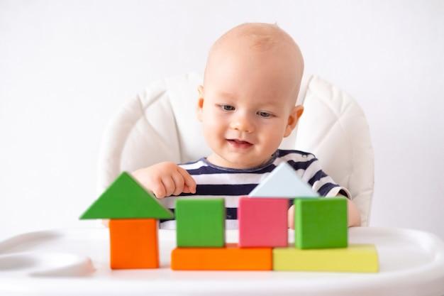 Маленький умный ребенок играет с красочными деревянными игрушками