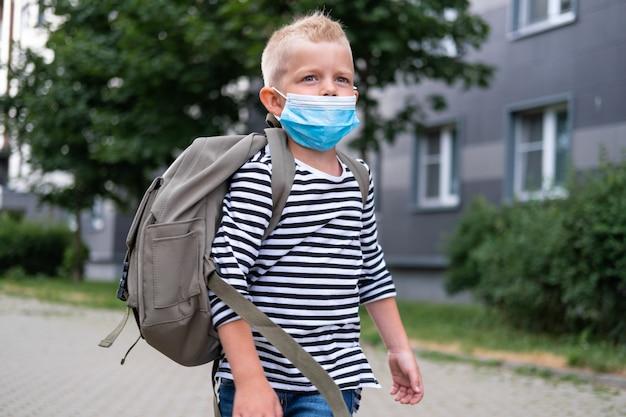 学校に戻る。マスクとバックパックを身に着けている男の子はコロナウイルスから保護し、安全です。パンデミックが終わって学校に通う子供。学生は新学期の準備ができています