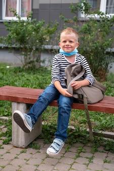 学校に戻る。マスクとバックパックを身に着けている幸せな少年は、コロナウイルスから保護し、安全です。パンデミック後、学校の近くに座っている子。学生は新年の準備ができています