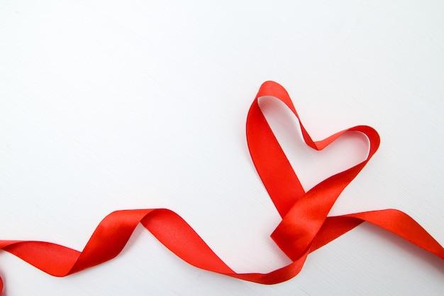白い木製の背景に赤いリボンで作られたハート形