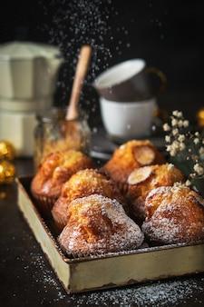 Домашние кексы с сахарной пудрой и кофе на темном фоне