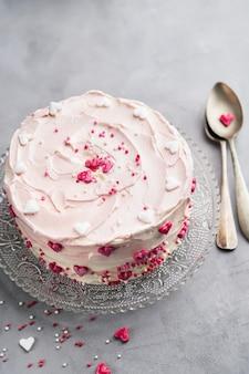 軽い背景に小さなハートとカラフルなスプーンが入ったケーキ。