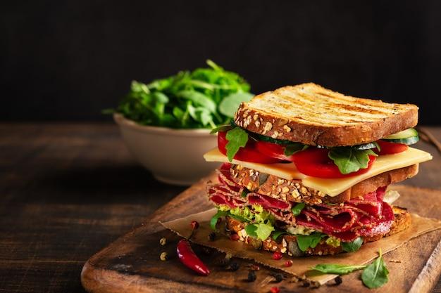 素朴な木製のカッティングボード上にサラミ、チーズ、新鮮な野菜が入ったサンドイッチ