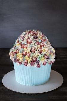 素朴な木製テーブルに霜降りの花の装飾と誕生日カップケーキケーキ。