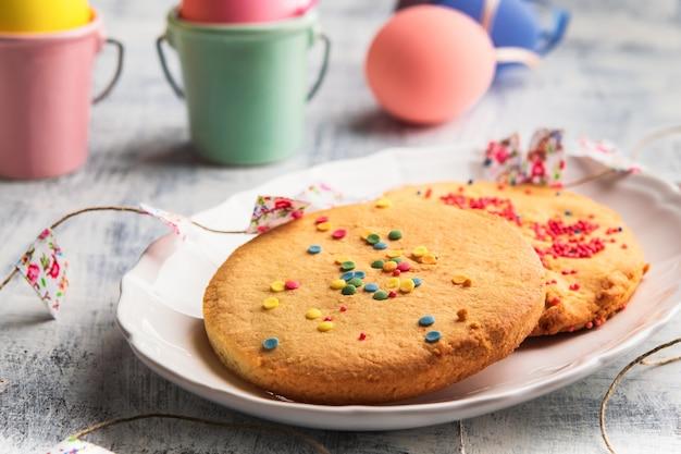 イースタースプリング白いプレートにカラフルなスプーンが付いたクッキー。イースターの幸せな概念。