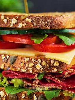 サラミ、チーズ、新鮮な野菜とおいしいサンドイッチのクローズアップ。