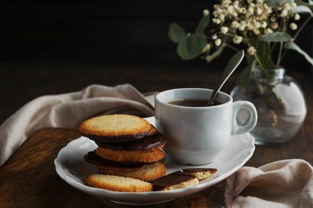 木製の背景にチョコレートクッキーと紅茶