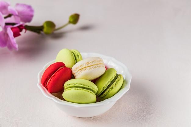 春の花、パステルカラーの明るい背景にマカロンまたはマカロンフランスのクッキー。