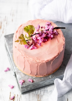 花、結婚式、誕生日およびでき事のための素朴なスタイルで飾られたロマンチックなピンクのケーキ。