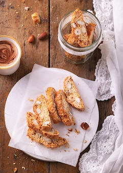 伝統的なペストリー、イタリアの自家製ビスコッティクッキーまたはカントゥチーニ、アーモンドナッツとコーヒー。