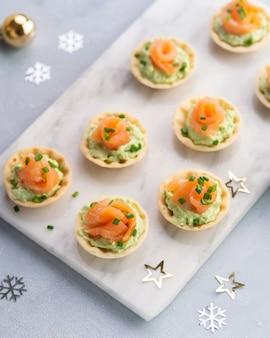 スモークサーモン、クリームチーズ、テキスト用のスペースと明るい背景にアボカドのカナッペ。クリスマスと新年の休日の背景概念。