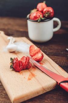 フルーツドライヤーラック用に準備された赤いスライスしたイチゴ。新鮮なイチゴをきれいにしてカット