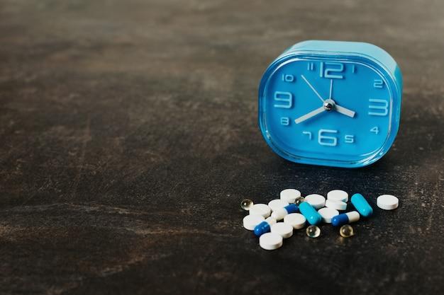 暗いテーブルに盛り合わせの丸薬と青い時計。健康薬物医学の概念