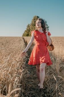 パンと純食料品の袋でパンと赤いドレスで幸せな若い女