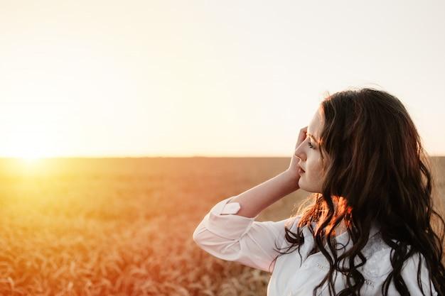 Молодая девушка в пшеничном поле на закате. медленная жизнь, концепция психического здоровья