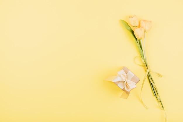 黄色のチューリップの花とパステル調の背景にギフトボックス。お祝い誕生日フラットレイアウト