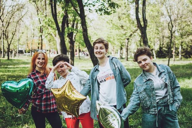 屋外の学生パーティー。公園で風船でパーティーを祝う笑顔の陽気なガールフレンドのグループ