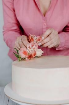 スタンドにピンクの花の結婚式の誕生日ケーキを飾る女性の手。