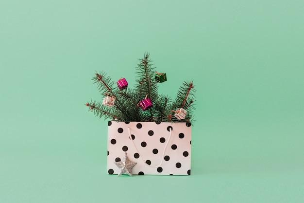 クリスマスの背景に木の枝、ギフトバッグに安物の宝石ボール