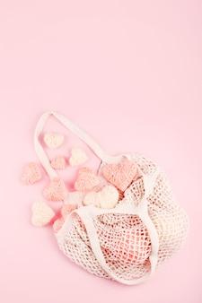 Многоразовая сетчатая сумка с белыми и розовыми вязаными сердечками на пастельном фоне
