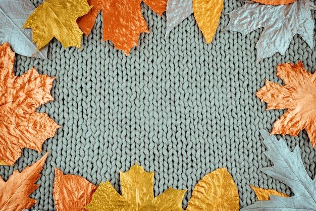 ニットの灰色の背景に黄金の葉のフレームと秋の組成