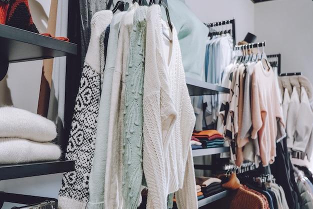Разная одежда на вешалках на полках на местном рынке, магазин, магазин