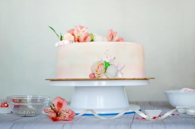 自然の新鮮な美しい花と繊細なピンクのウェディングケーキ