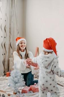 ボクシングデー。小さな女の赤ちゃんとママはクリスマスツリーの近くのピンクのギフトボックスを開梱します