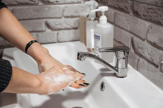 Гигиена рук. как мыть руки с мылом и водой. женщины моют руки с антибактериальным мылом в домашней ванной комнате. предотвратить распространение микробов.