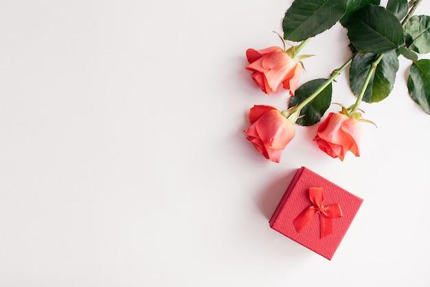 白い背景に新鮮な赤いバラと赤い弓のギフトボックス