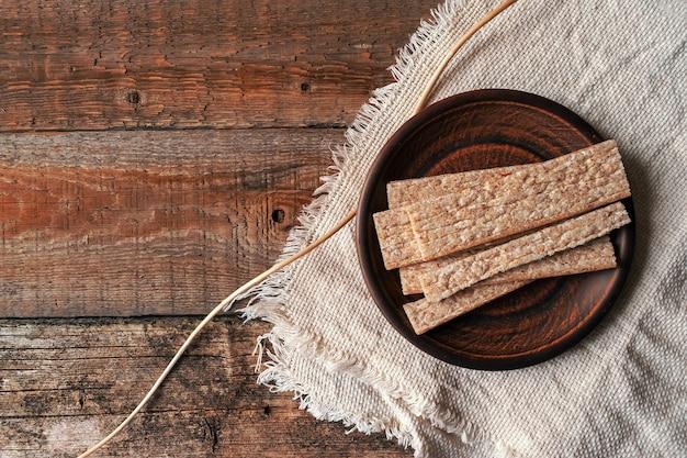 丸い茶色の粘土板上に全粒粉のパン