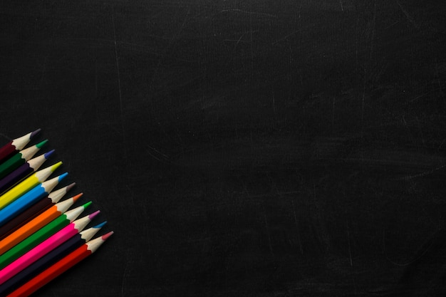 黒の黒板の背景に多色の木製鉛筆