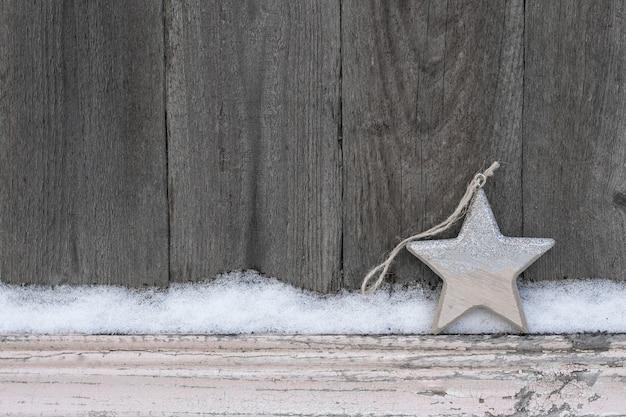 木製のクリスマススターが付いている錆びた冬の背景