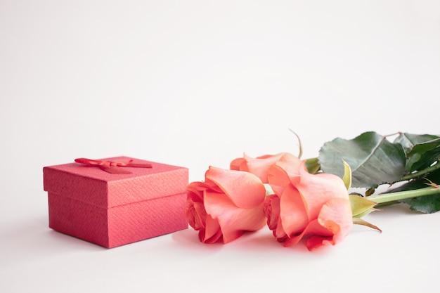 新鮮な赤いバラと赤い弓ギフトボックス