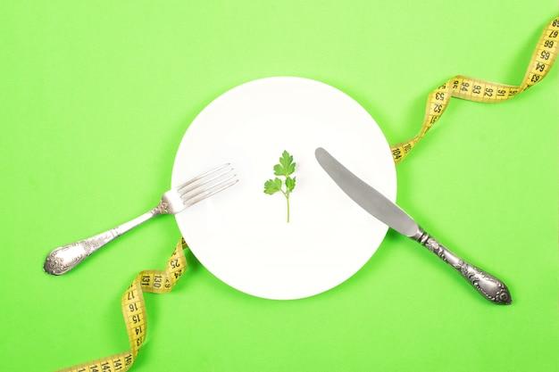 ダイエット、減量、健康的な食事、フィットネスの概念を量ります。