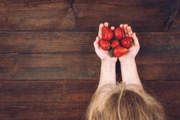 子供の手の中のイチゴ