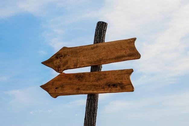 Два деревянных стрелка указатели макет на голубом небе