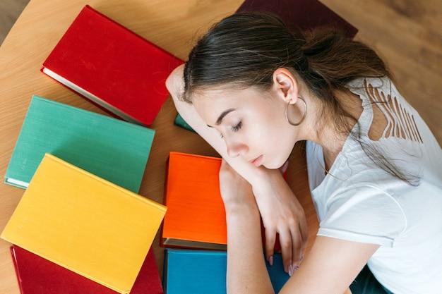 Усталый студент спит на книге в библиотеке