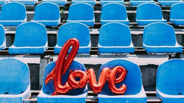 Люблю красный воздушный шар из фольги на синих сиденьях стадиона
