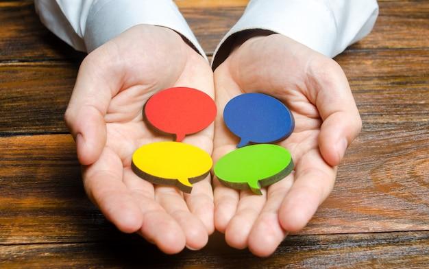 Мужчина держит в руках разноцветные речи пузыри. прислушиваться к другим мнениям и точкам зрения