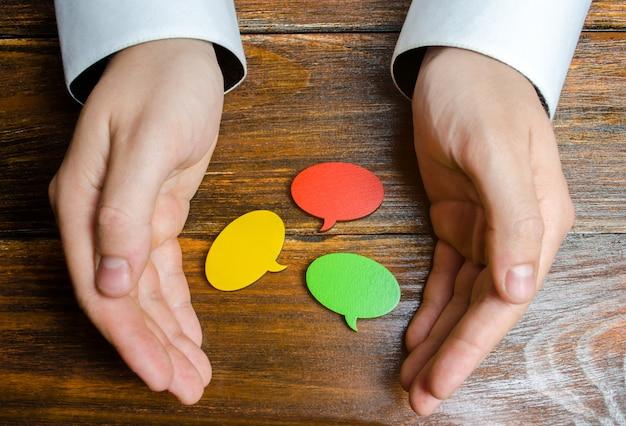 Мужчина собирает в руках разноцветные речевые пузыри. слушайте другие мнения