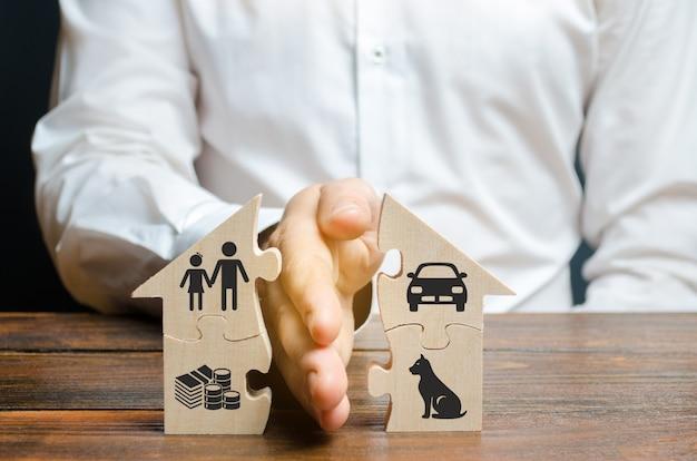 Мужчина делит дом ладонью с изображениями имущества, детей и домашних животных