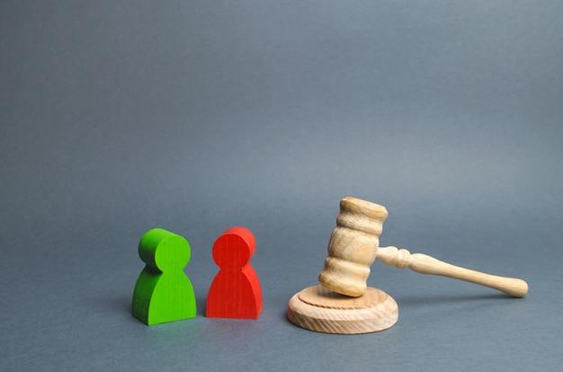 Две фигуры противников стоят возле молотка судьи. разрешение конфликтов в суде