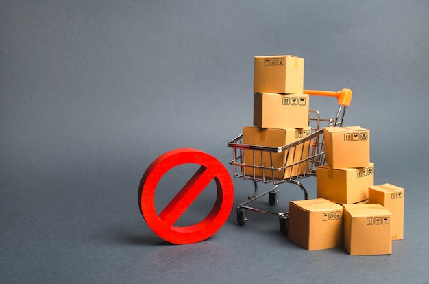 Картонные коробки, тележка супермаркета и красный символ нет. эмбарго, торговые войны. ограничение