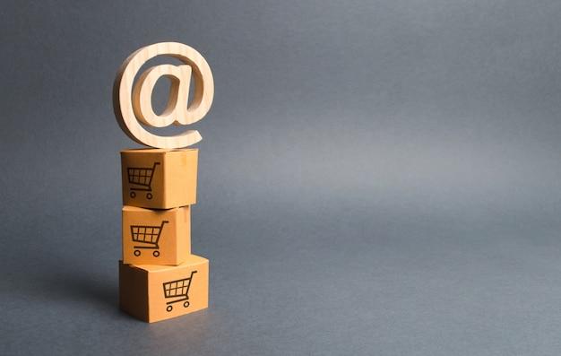 Куча картонных коробок с рисунком магазинных тележек и символом электронной коммерции ат