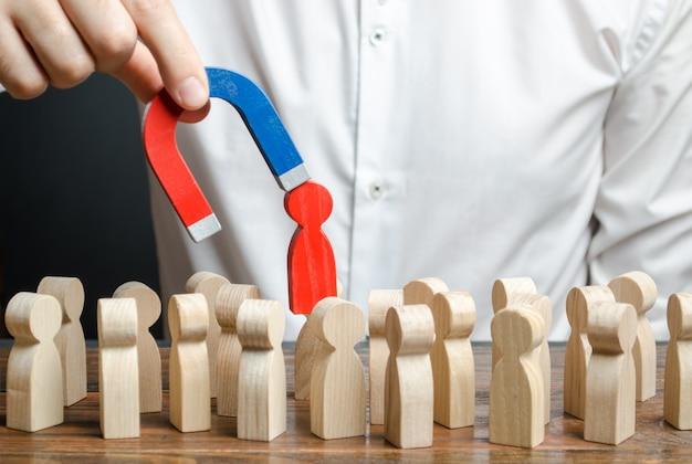 ビジネスマンは磁石の助けを借りて群衆から男の赤い姿を引き出します。毒性