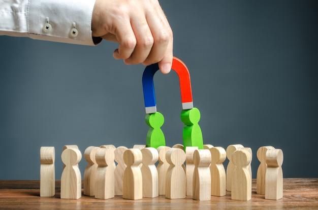 磁石を持ったビジネスマンは群衆の中から人々の緑色の数字を引き出します。新入社員の募集