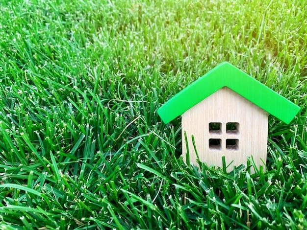 緑の芝生の上のミニチュア木造住宅。