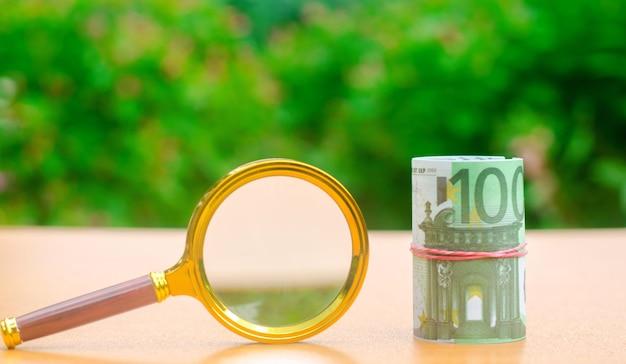 ユーロ紙幣と虫眼鏡。